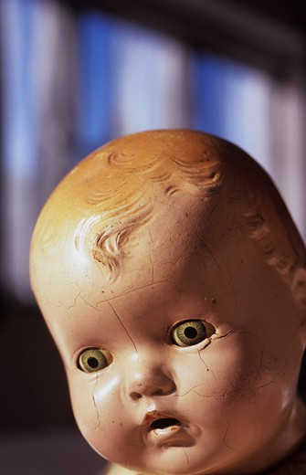 Stock Photo: 1318R-1509 UK, England, Norfolk, Close up of face of traditional baby doll with pale green eyes and open mouth and cracks with windows and blue sky beyond