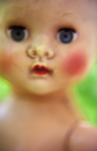 Stock Photo: 1318R-1510 UK, England, Norfolk, Atmospheric close up of face head and shoulders of traditional baby doll with staring dark blue eyes and red lips and cheeks