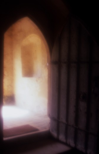 Stock Photo: 1318R-1511 UK, England, Norfolk, Atmospheric view of heavy ancient timber door standing open with view thru Early English Gothic archway to sunlit room