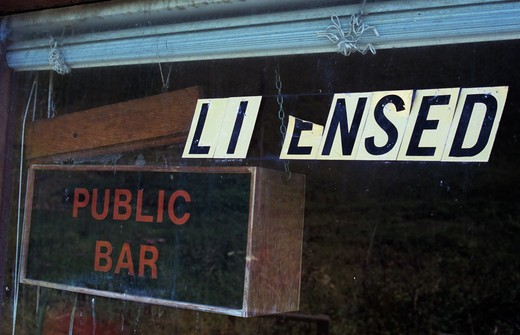 Stock Photo: 1318R-1528 UK, Wales, Dyfed, Detail of window with rundown signs stating Licensed and Public Bar with general air of neglect