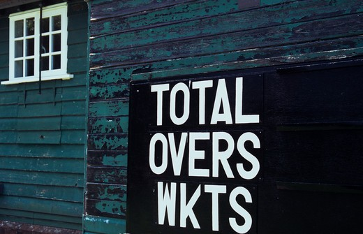 Stock Photo: 1318R-1541 UK, England, Norfolk, Scoreboard on side of blue painted wooden cricket pavilion with blank slots labeled Total Overs and Wickets