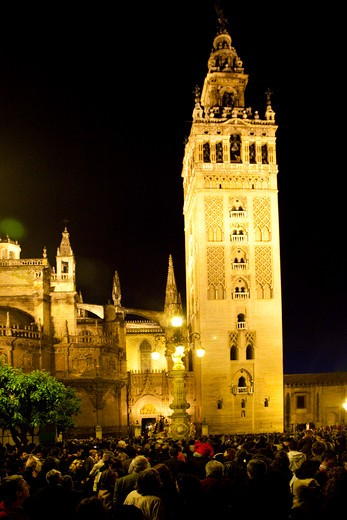 Spain, Seville, Low angle view of Seville Cathedral at night with crowd gathered for Holy Week celebrations : Stock Photo