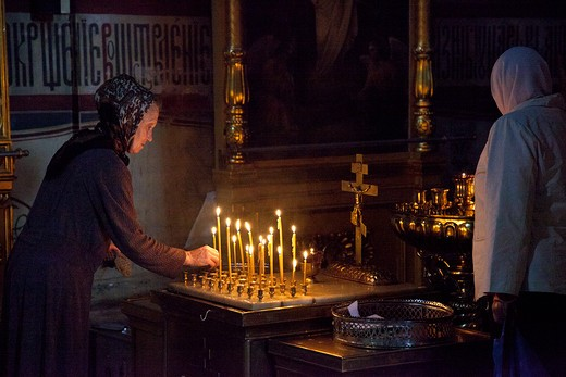 Women lighting candles inside the Assumption Cathedral, St. Sergius Monastery, Sergiyev Posad, Moscow Oblast, Russia : Stock Photo
