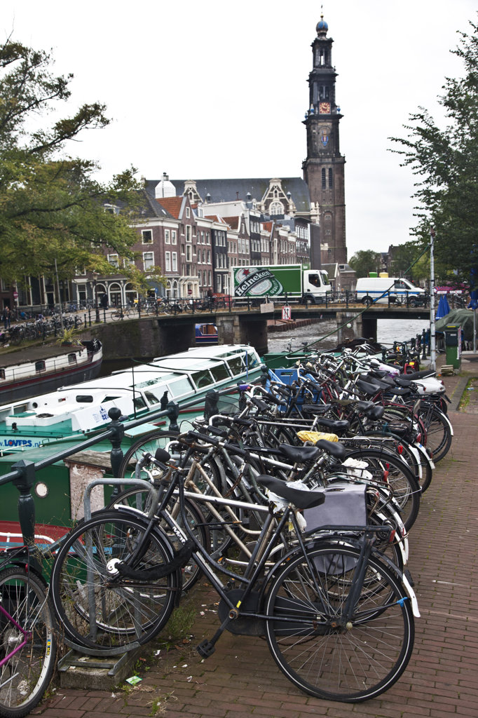 Stock Photo: 1323-1918 Bicycles along a canal with a church in the background, Westerkerk, Amsterdam, Netherlands