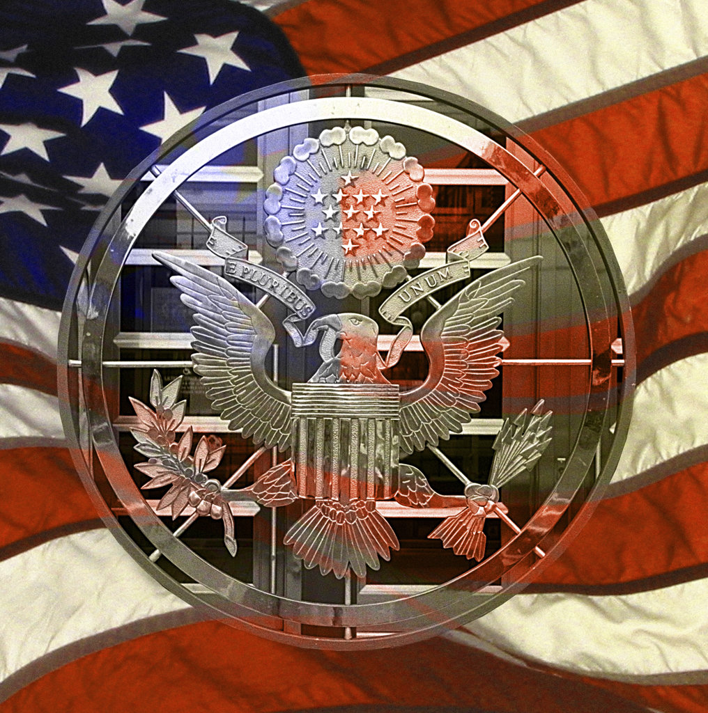 Close-up of a coat of arms with an American flag in the background : Stock Photo