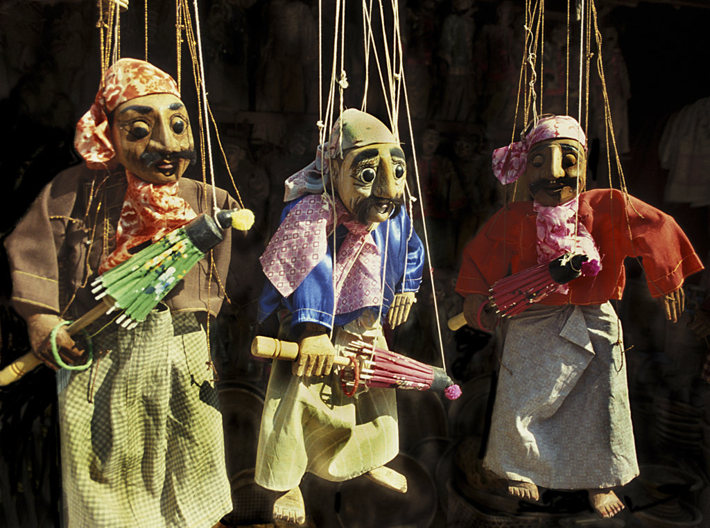 Close-up of three puppets hanging on strings : Stock Photo