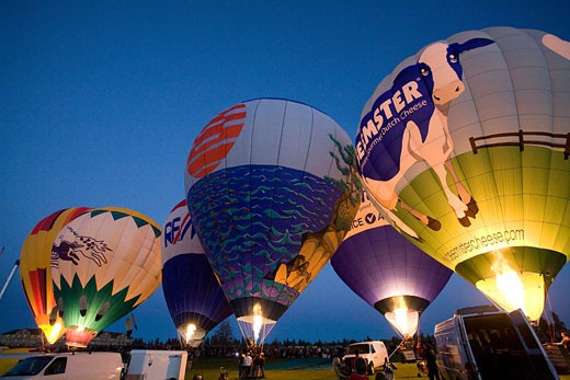 Low angle view of hot air balloons being inflated with a propane heater, Bend, Oregon, USA : Stock Photo