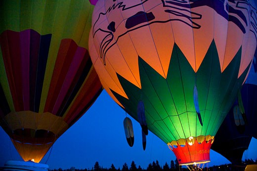 Stock Photo: 1323-823 Low angle view of hot air balloons being inflated with a propane heater, Bend, Oregon, USA