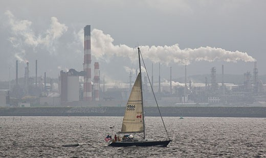 Stock Photo: 1323-841 Sailboat in a bay with an oil refinery in the background, Bay Of Fundy, St. John, New Brunswick, Canada