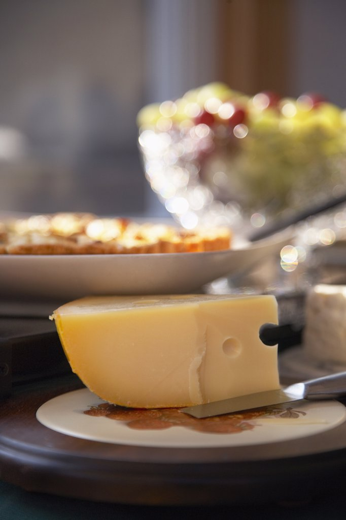 Stock Photo: 1329-1225 Close-up of wedge of Swiss cheese with other food on a plate