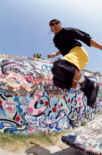 Low angle view of a young man performing stunts with inline skates : Stock Photo