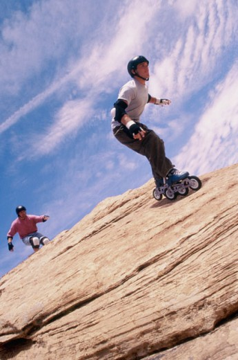 Low angle view of two young men inline skating on a rock : Stock Photo