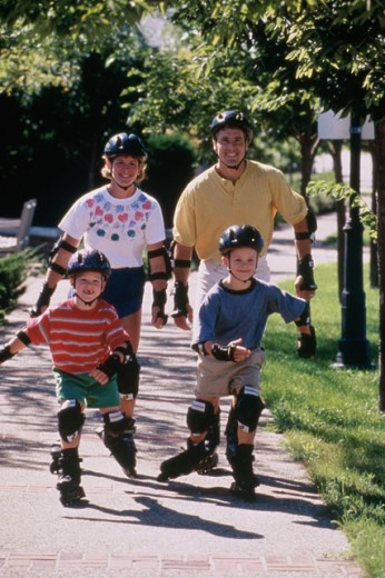 Stock Photo: 1329-643 Parents with their two sons inline skating on a walkway