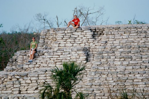 Young couple sitting on a stone wall, Mayan Ruins, Mexico : Stock Photo