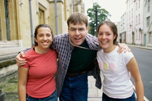 Portrait of a young man and two teenage girls smiling, London, England : Stock Photo