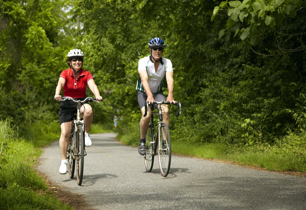 Stock Photo: 1329R-1410 Man and woman leisurely riding bikes on path through woods