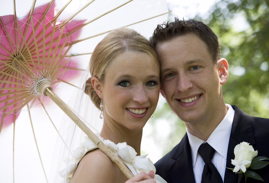 Stock Photo: 1329R-1429 Bride and groom in their mid 20's with bride holding parasol