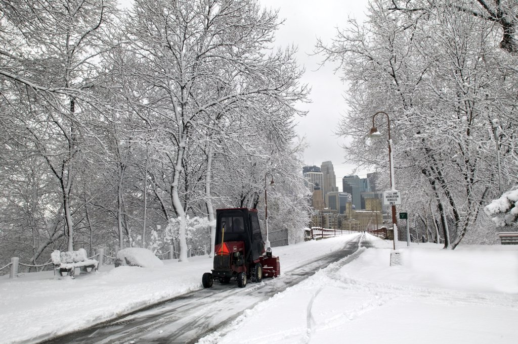 USA, Minnesota, Minneapolis, Red snow plow in white winter park looking at skyline of city : Stock Photo