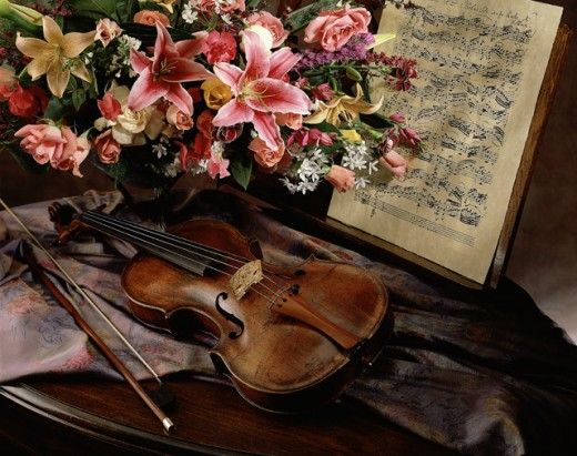 Violin and a bow near a vase of flowers and sheet music : Stock Photo
