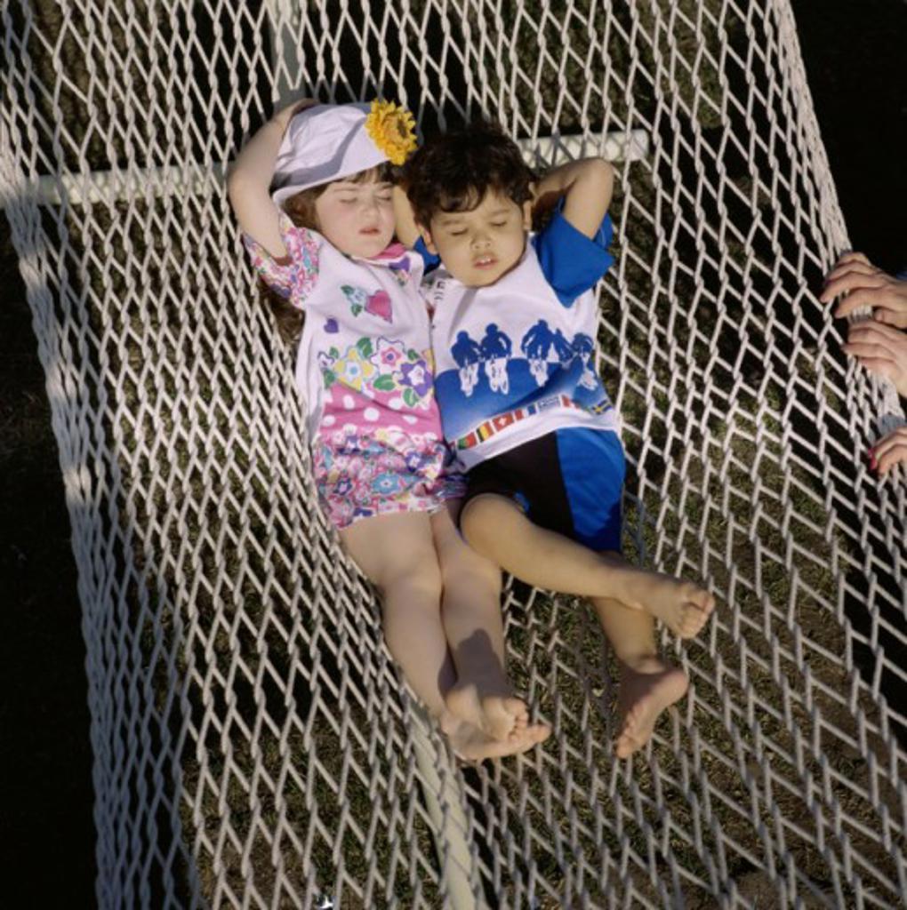 Stock Photo: 1329R-569 Two children sleeping in a hammock