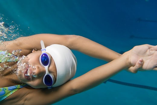Close-up of a girl swimming in a swimming pool : Stock Photo