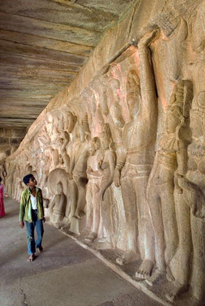 Stock Photo: 1340-1048 Teenage boy looking at carvings at a temple, Krishna Mandapa, Mahabalipuram, Tamil Nadu, India