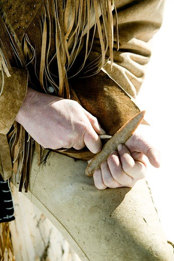 Stock Photo: 1341R-2052A Close-up of a hunter's hand knapping a piece of stone using an obsidian stone, Jackson, Wyoming, USA
