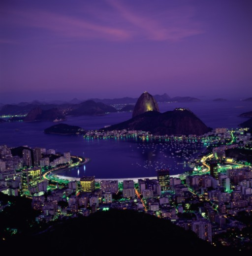 Aerial view of buildings in a city lit up at night with mountains in the background, Sugarloaf Mountain, Rio de Janeiro, Brazil : Stock Photo