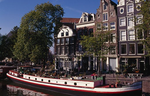 Boat docked in a canal in front of townhouses, Prinsengracht, Amsterdam, Netherlands : Stock Photo