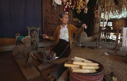 Senior woman working on a spinning wheel, Bagan, Myanmar : Stock Photo