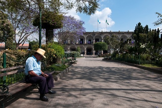 Man sitting in a park, Parque Central, Antigua, Guatemala : Stock Photo
