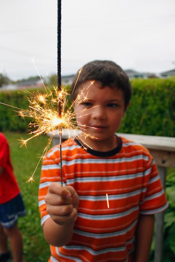 Boy holding a sparkler : Stock Photo