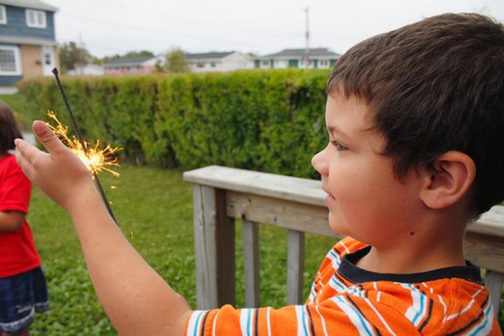 Stock Photo: 1346-1254 Boy holding a sparkler