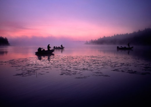 Stock Photo: 1346-718 Silhouette of three people fishing in a lake