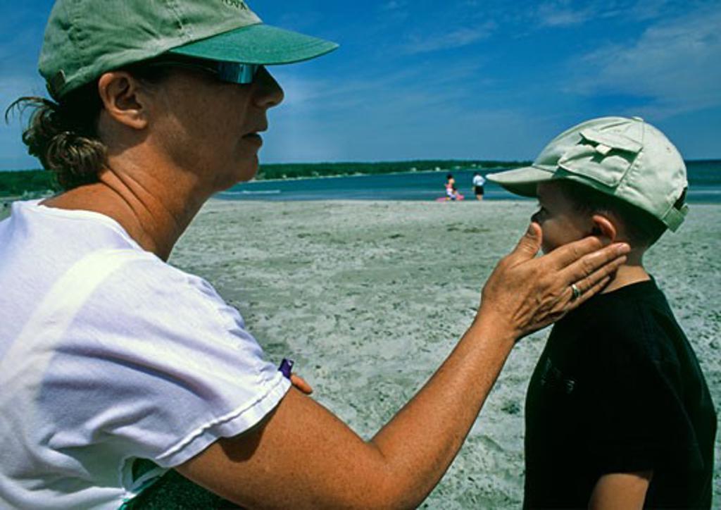 Stock Photo: 1346-793 Senior woman applying suntan lotion to her grandson's face
