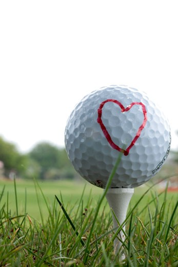 Stock Photo: 1346-844 Close-up of a golf ball on a tee with a heart shape drawn on it