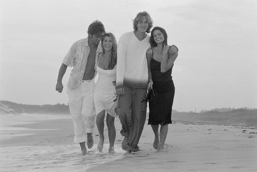 Two young couples walking on the beach : Stock Photo