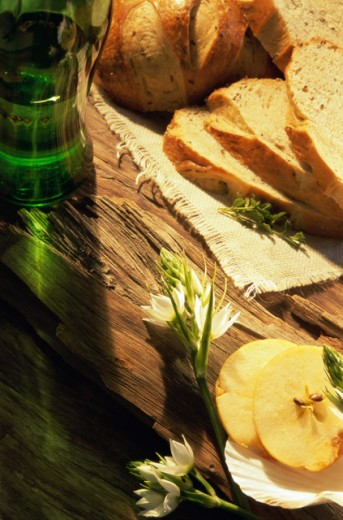 Close-up of bread slices with a wine bottle and slices of fruit : Stock Photo