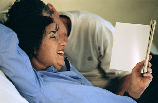 Stock Photo: 1350-860 Close-up of a mid adult woman holding a book and a mid adult man leaning over her