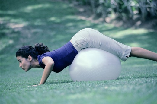 Stock Photo: 1350-953 Side profile of a young woman exercising on a fitness ball