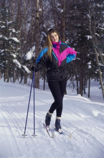 Portrait of a young woman holding ski poles : Stock Photo
