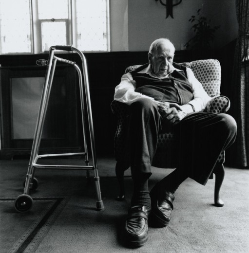 Stock Photo: 1368-107 Low angle view of a senior man sitting in an armchair with a walker beside him