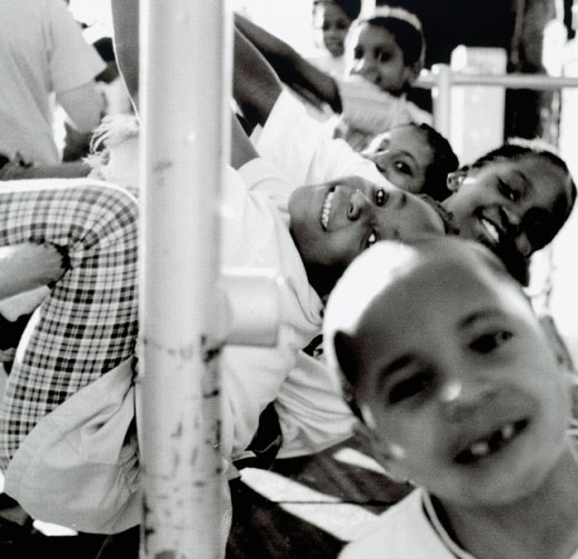 Group of children hanging on a railing and smiling : Stock Photo