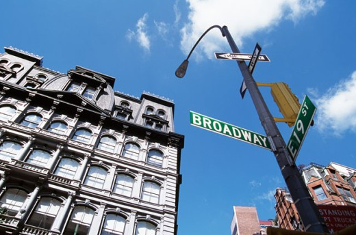 Low angle view of a street light with directional signs, New York City, New York, USA : Stock Photo