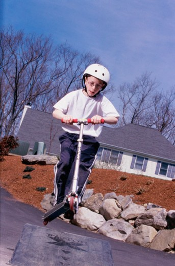 Low angle view of a boy jumping on a ramp with a push scooter : Stock Photo
