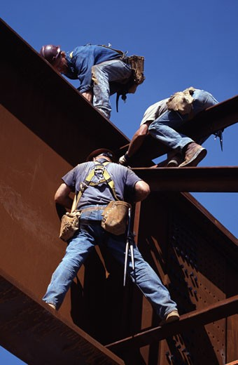 Stock Photo: 1370-41973 Low angle view of three steelworkers bolting cross braces between plate girders