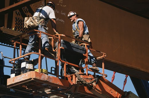 Low angle view of two steel workers bolting girders at a bridge construction site : Stock Photo