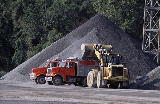 Stock Photo: 1370-42300 Earth mover with dump trucks at a construction site