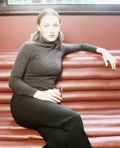 Portrait of a young woman sitting on a couch and holding a glass of juice : Stock Photo