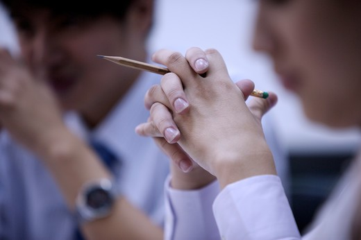 Stock Photo: 1397R-69113 Close-up of young woman's hands holding a pencil